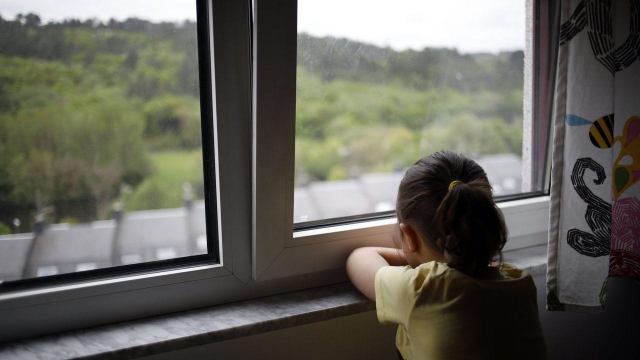 Una niña mira por la ventana durante el confinamiento