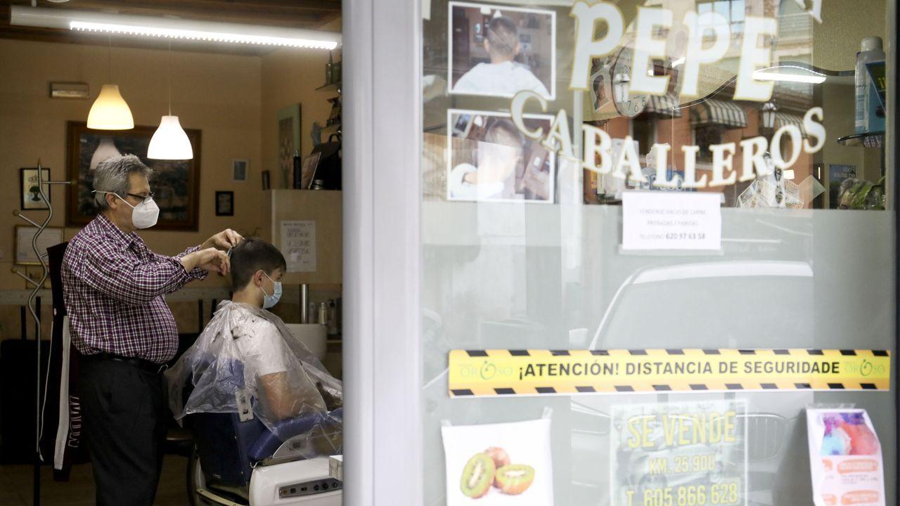 José María Barreiro corta el pelo a un cliente en la Peluquería Pepe de Sigüeiro (Oroso)