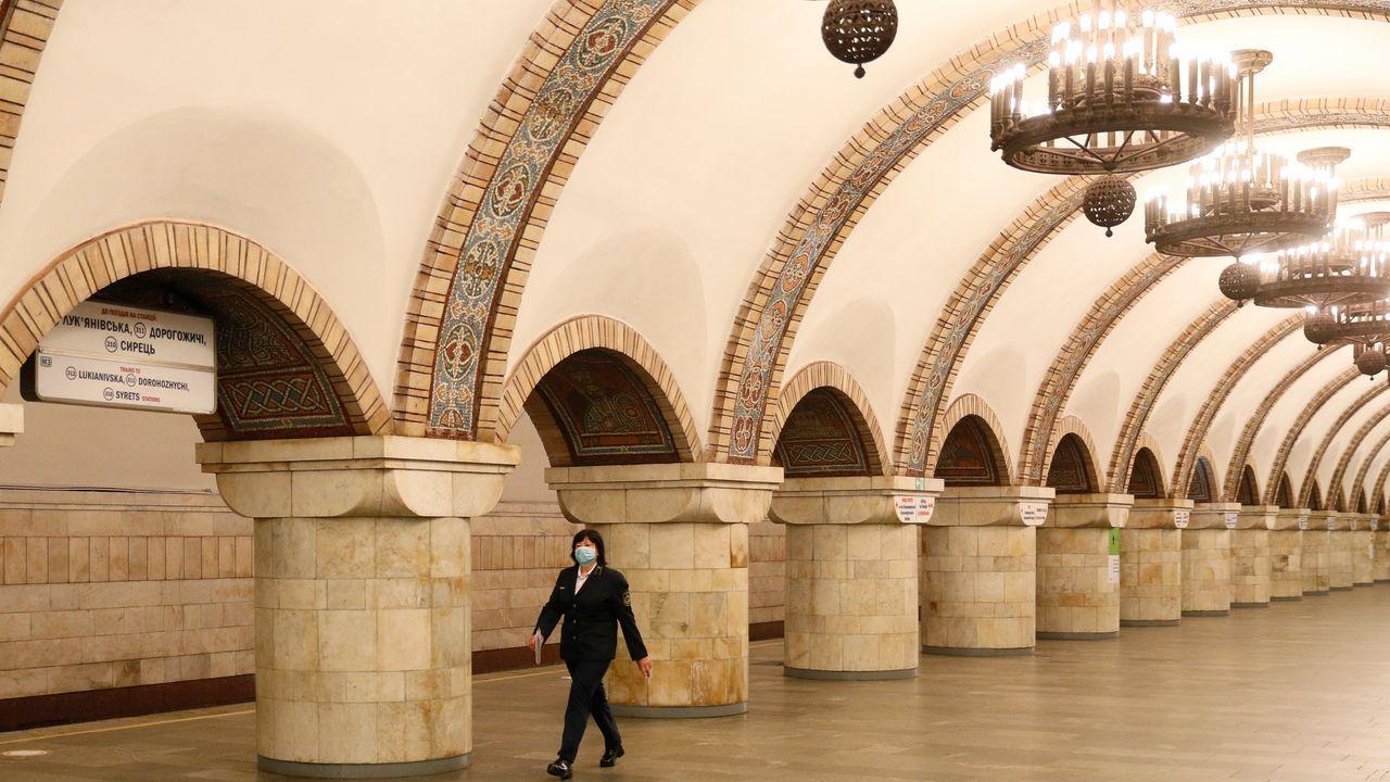 Una trabajadora camina por la vacía estación central del metro de Kiev, cerrada por la pandemia
