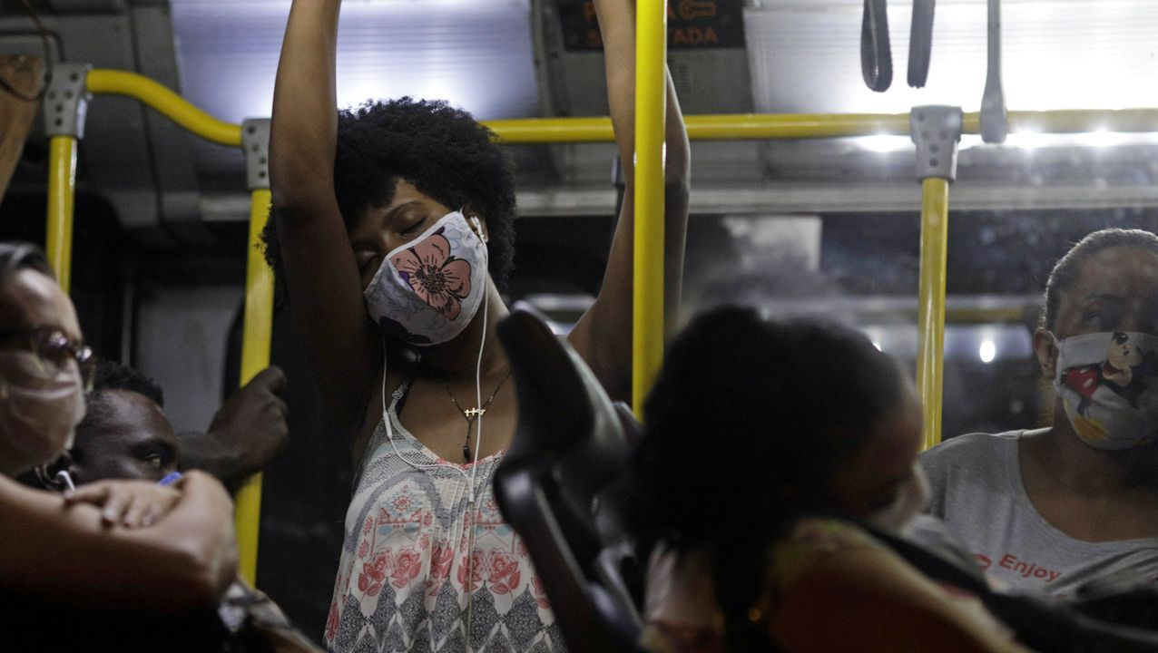Pasajeros de un autobús en Río de Janeiro, portando mascarillas de protección