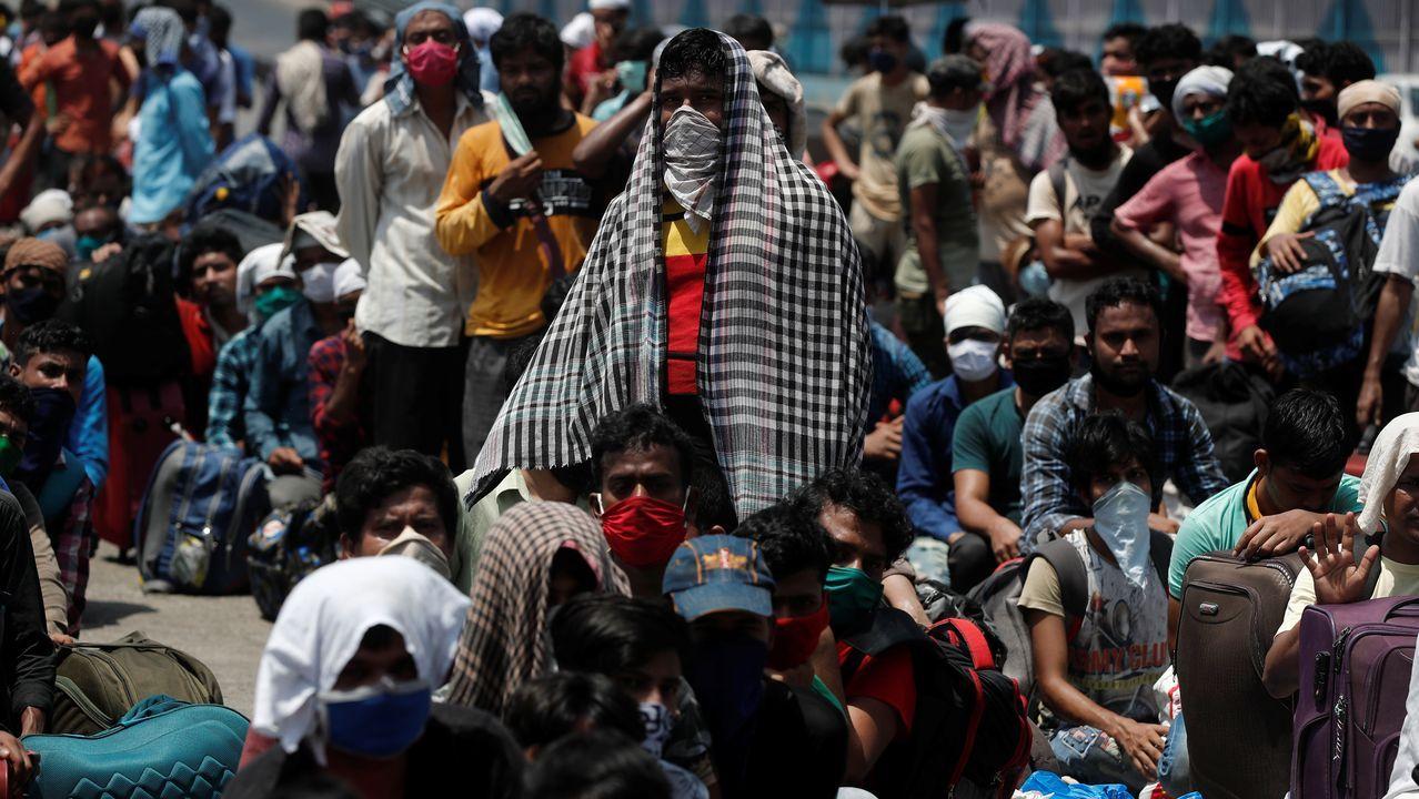 Decenas de personas, muchas con mascarillas improvisadas, hacen cola para tomar un tren en Bombai, India