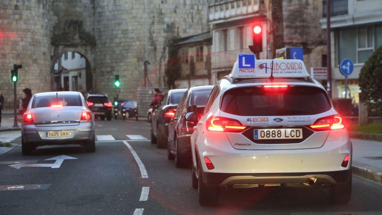 Un coche de autoescuela circulando por Lugo