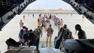 Militares españoles y ciudadanos afganos subiendo a bordo de un avión militar para ser evacuados de Afganistán