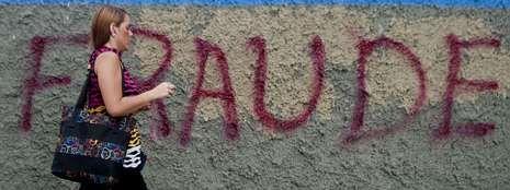 Una mujer pasa por delante de un muro con una pintada alusiva a las irregularidades en las elecciones ganadas por Maduro.