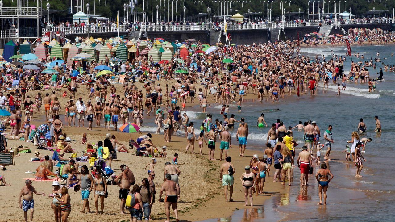 Aspecto de la playa asturiana de San Lorenzo de Gijón hoy a mediodía, que presentaba un lleno por los más de 25 grados de temperatura y los pocos días de sol en el principado.