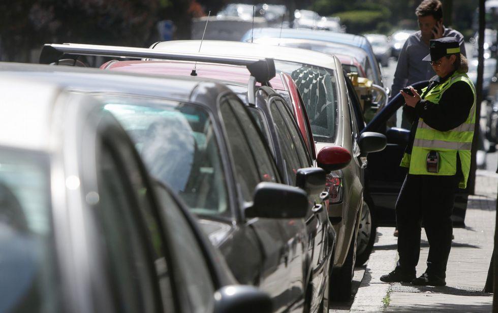 Una operaria del servicio de la ORA revisa los tiques de una fila de coches estacionados.