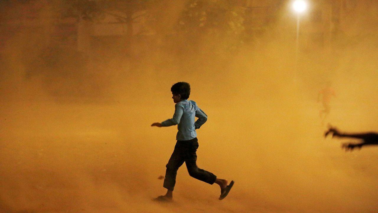 Un niño corre para protegerse de una tormenta de arena en Nueva Delhi, en India