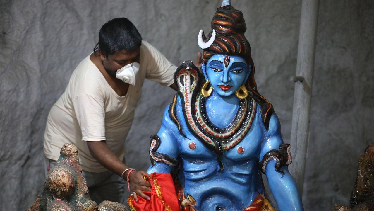 Un trabajador con mascarilla limpia una estatua en un santuario de Bohpal, India