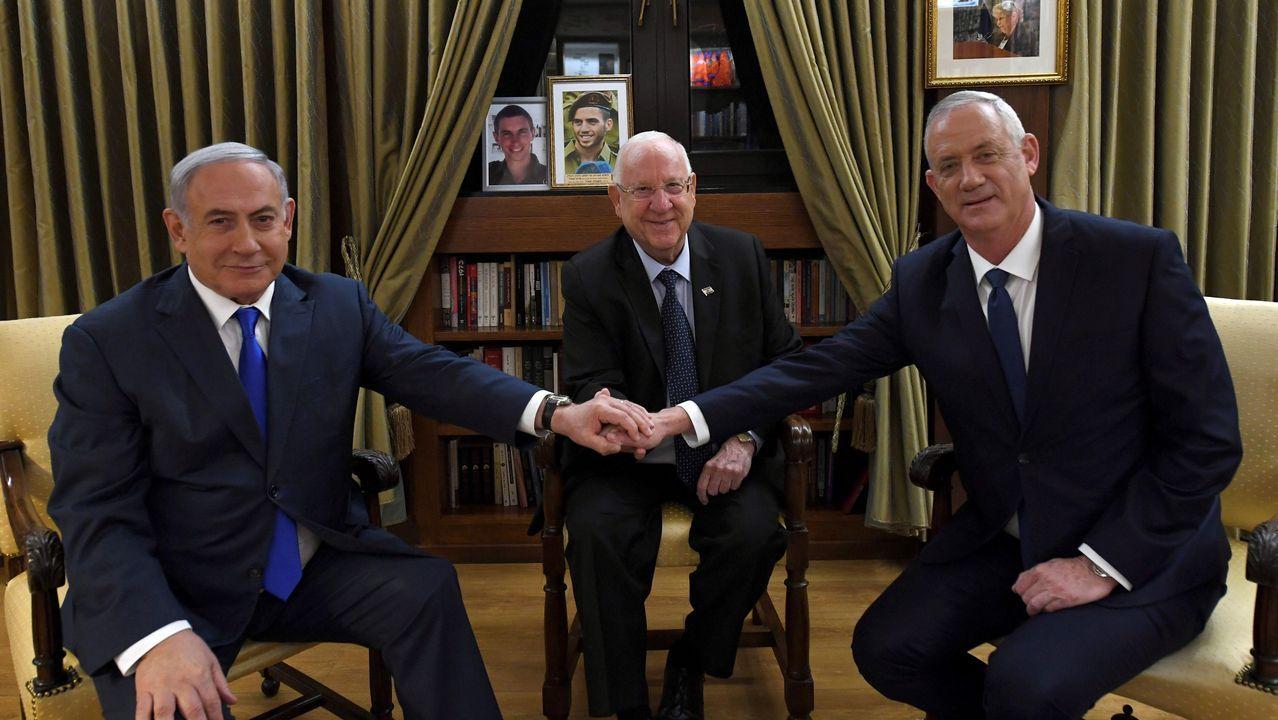 Benjamín Netanyahu y Benny Grantz se dan la mano frente al presidente Rivlin