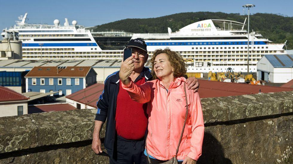 Dos cruceristas tomándose una foto en Ferrol con el buque de fondo