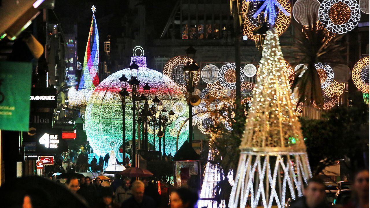 Foto dunha rúa con led de decoración e iluminación de diferentes temperaturas de cor. As zonas máis iluminadas do chan son as que están baixo un farol ou preto dun escaparate