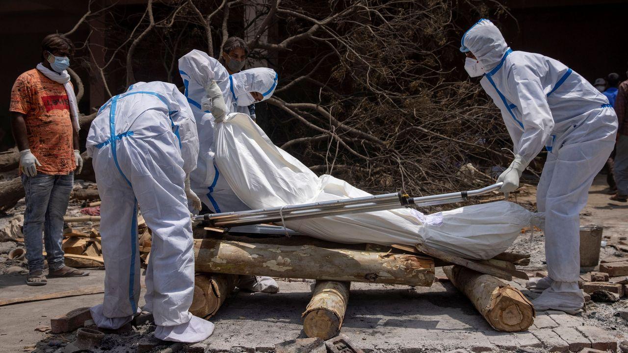 India suma un nuevo máximo de casos al día con casi 400.000 contagios oficiales.Un grupo de personas, preparando el cuerpo de una de las víctimas mortales del covid-19 para proceder a su cremación