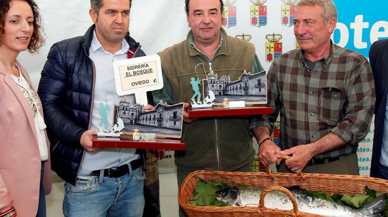El pescador Fernando López Castro (c) posa con el 'campanu', y con el representantes de la sidrería El Bosque (2i)