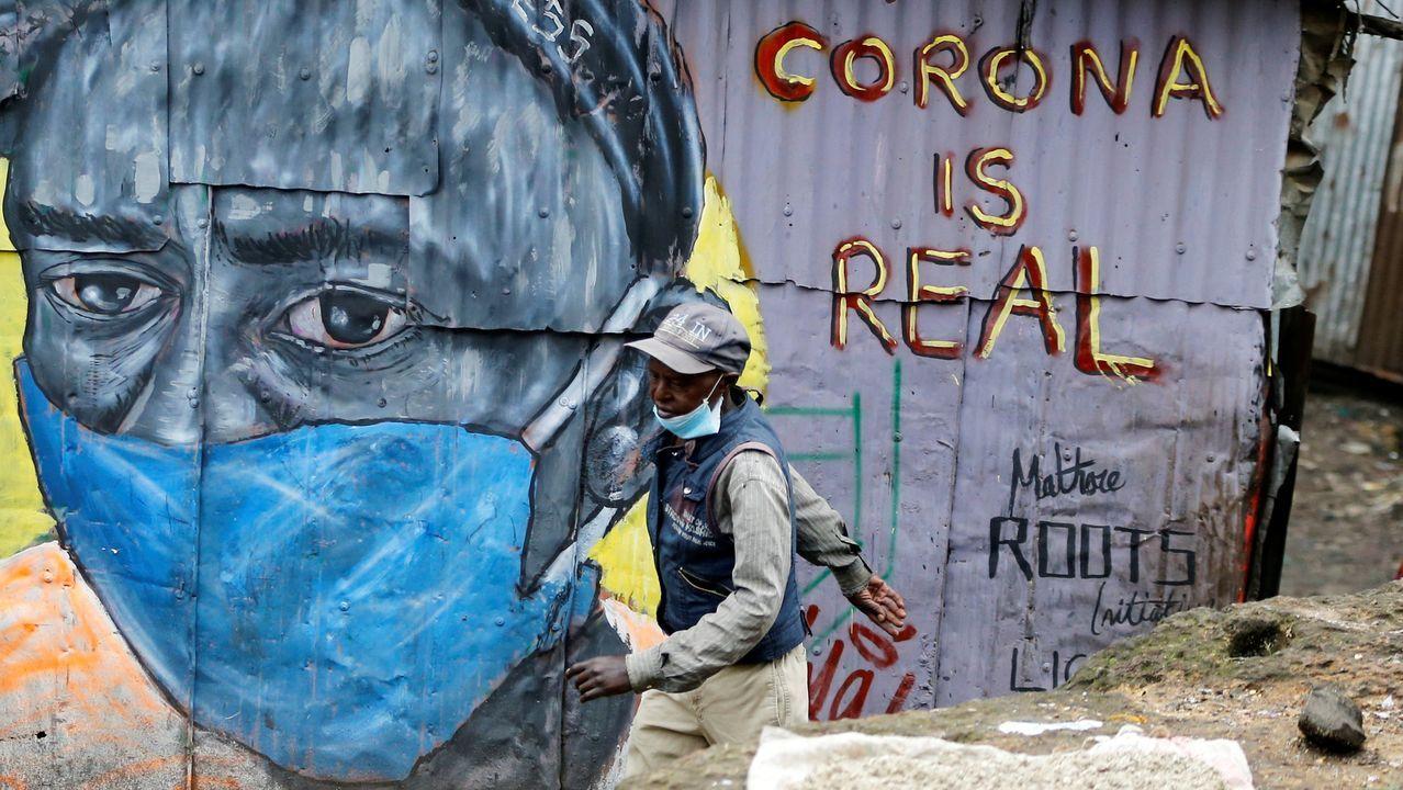 Un hombre pasa delante de un grafiti que alerta sobre el coronavirus en Nairobi