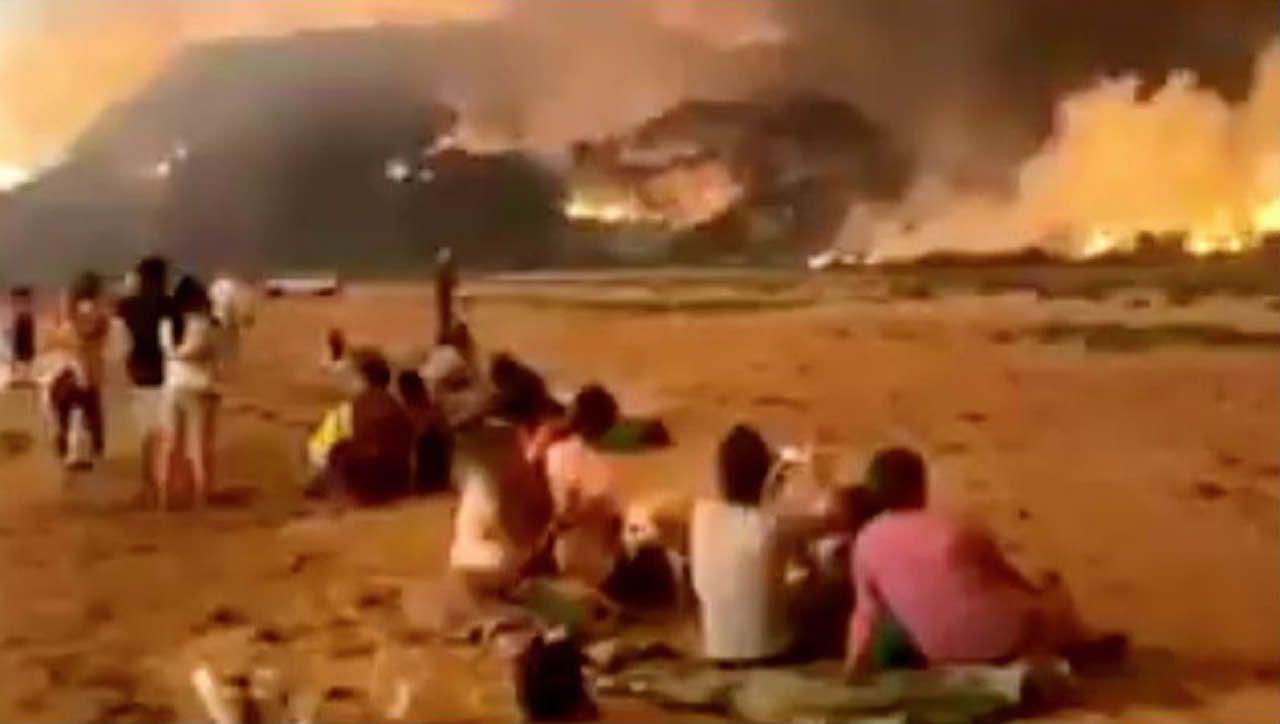 Un paisaje adulterado por el fuego.Personas refugiadas de los incendios en las playas