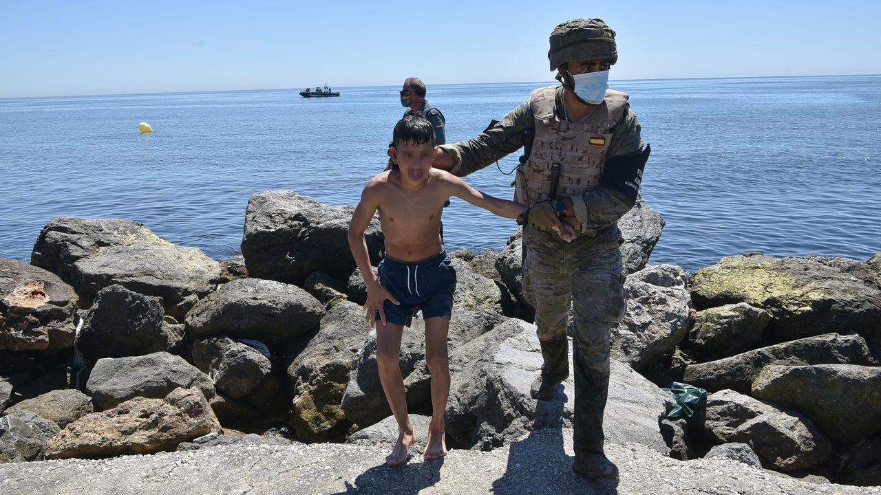 Sánchez confirma que el Gobierno indultará mañana a los presos del «procés».Un militar del ejército español ayuda a un menor migrante procedente de Marruecos a su llegada a Ceuta