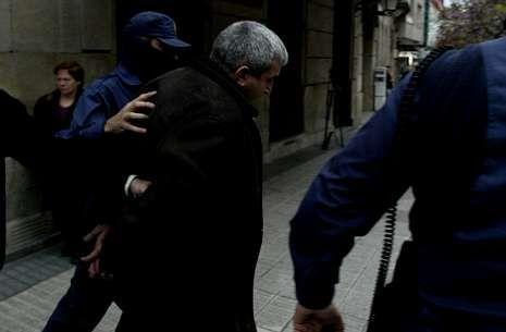 Uno de los detenidos es escoltado durante un registro en una tapería de Vigo en el 2004.