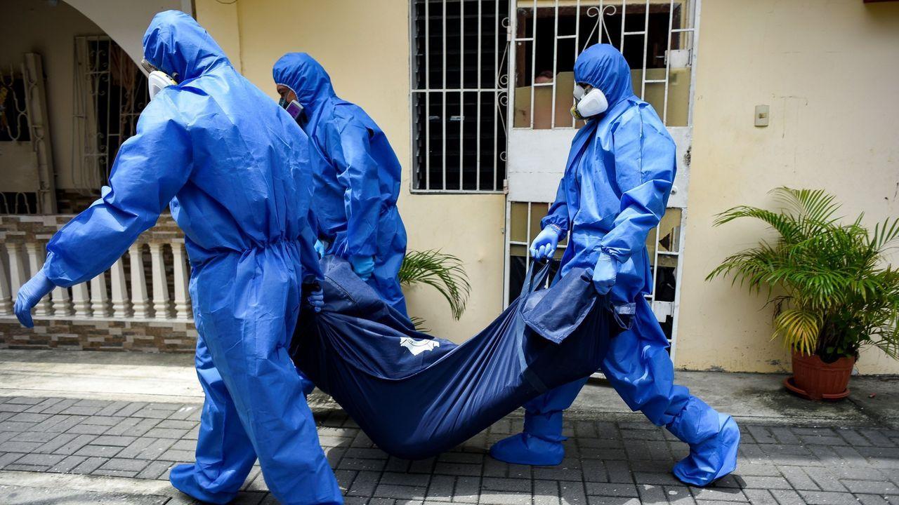 Policías ecuatorianos recogen un cadaver de una casa en Guayaquil, el llamado Wuhan sudamericano