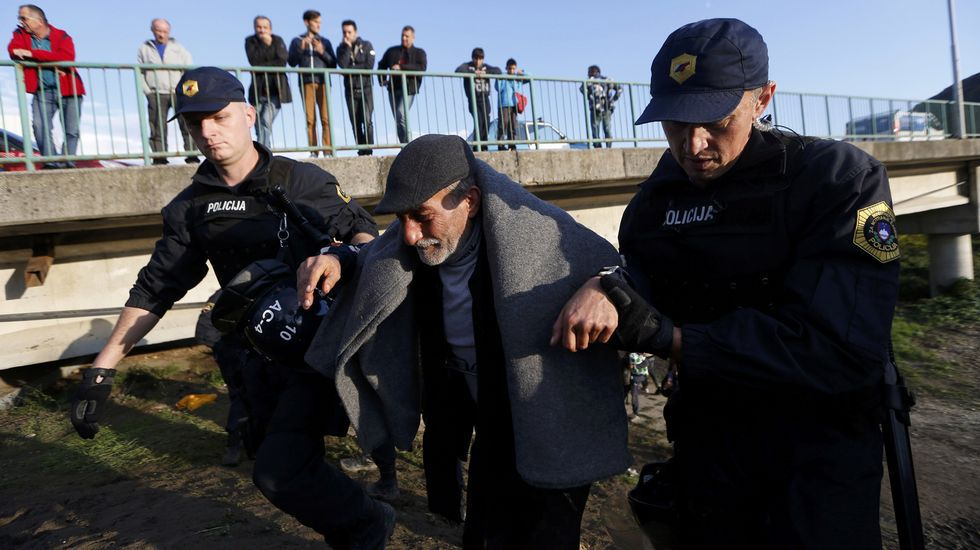 Dos policías ayudan a un refugiado en Brezice, Eslovenia