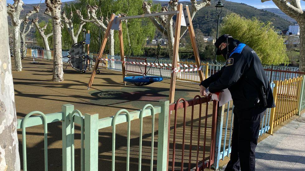 Así está Ourense en el primer día laborable tras decretarse el estado de alarma.Un policía, clausurando el parque infantil del Malecón