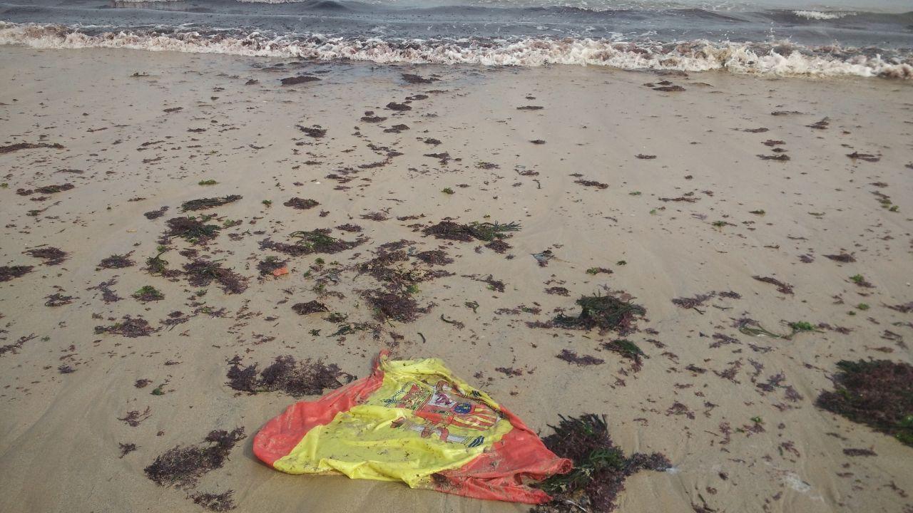 Bandera de España arrastrada por la marea, en la playa de San Lorenzo de Gijón