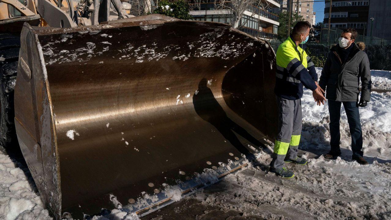 Una excavadora militar y varios operarios retiran la nieve en el Ministerio de Defensa, en el madrileño Paseo de la Castellana