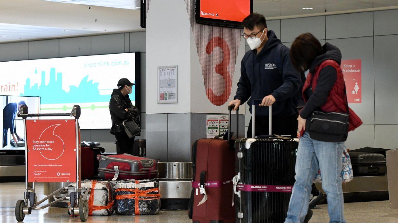 Imágenes de la pandemia en el mundo.Pasajeros, recogiendo sus equipajes en el aeropuerto de Sídney