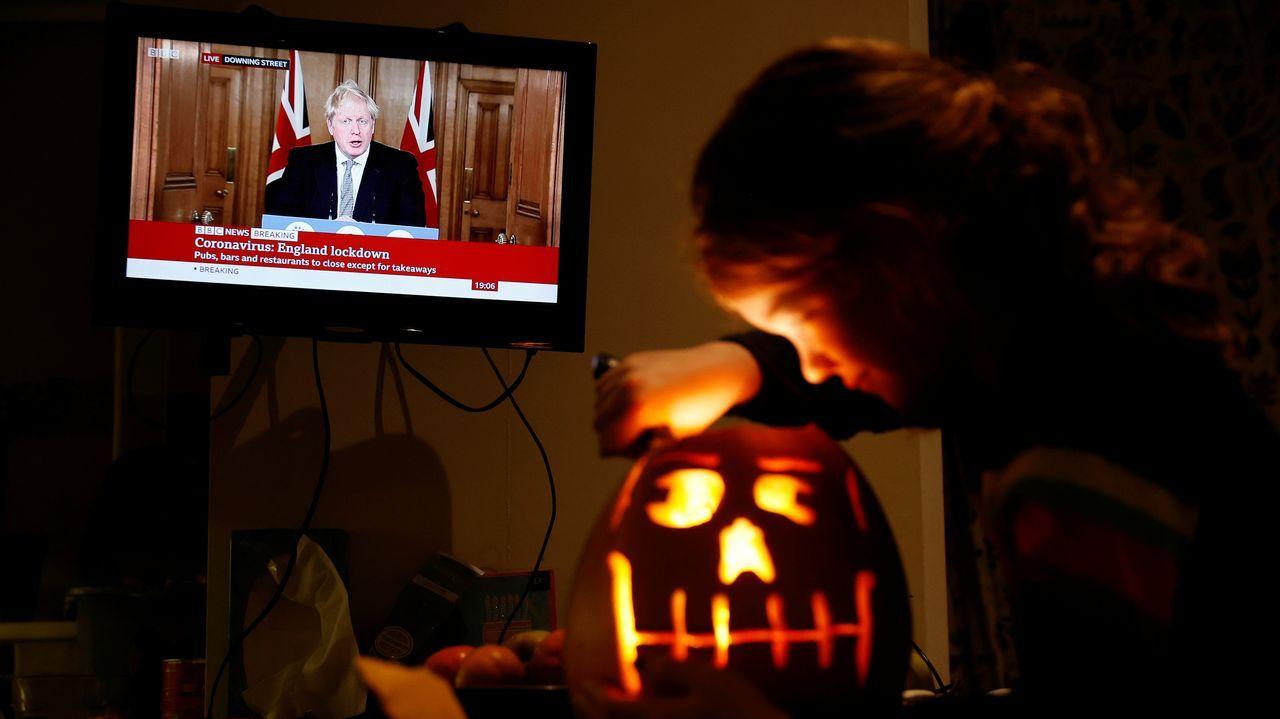 Una niña modela una calabaza de Halloween mientras Boris Johnson anuncia el confinamiento de Inglaterra
