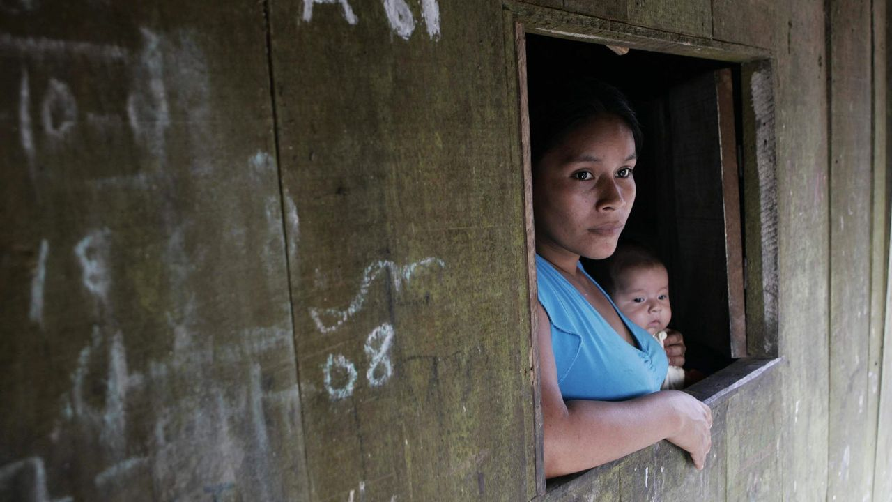Una mujer indígena amazónica con su bebé, en el distrito de Belén, en la ciudad de Iquitos