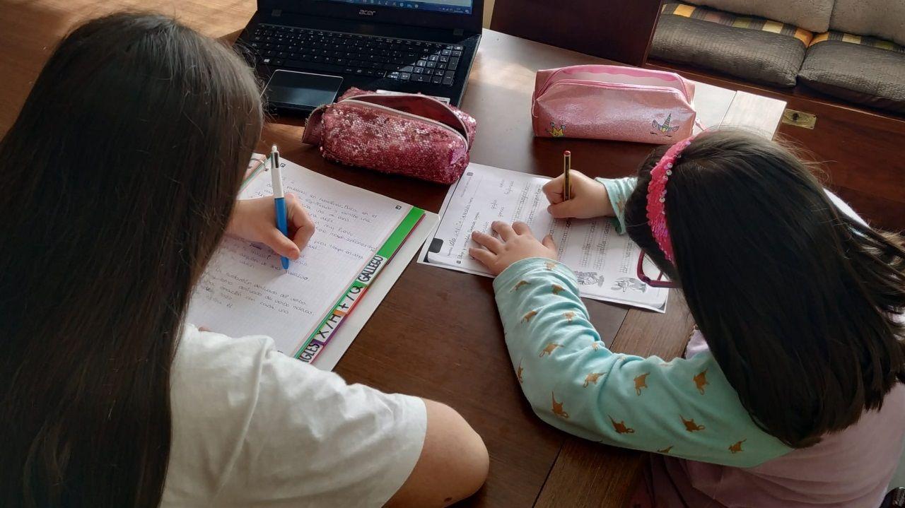 Lucía, alumna de Secundaria,  y Lola, de Primaria, hacen tareas escolares en el comedor de su casa