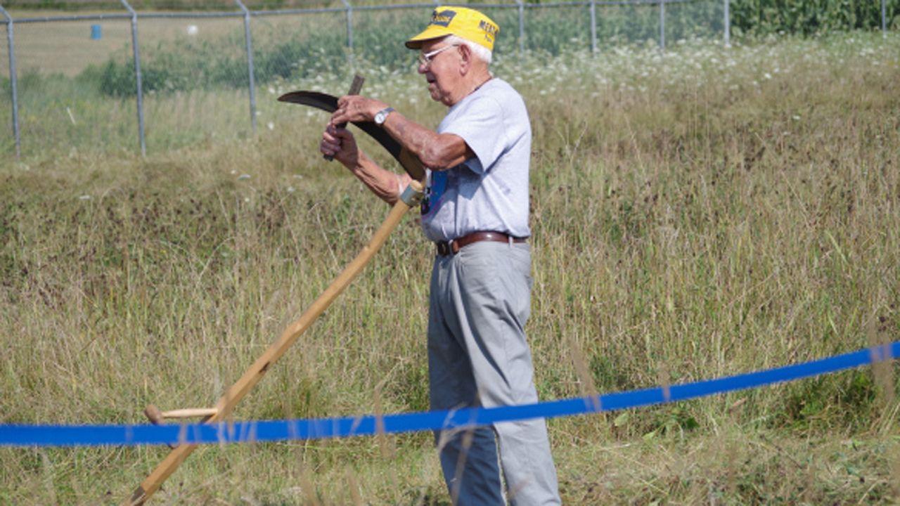 Uno de los creadores de un concurso de siega manual en Vermont afilando su hoja