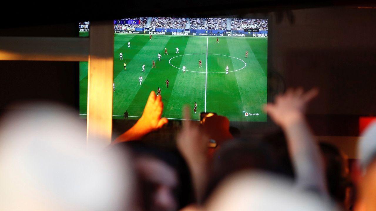 Gente viendo un partido de futbol en un bar