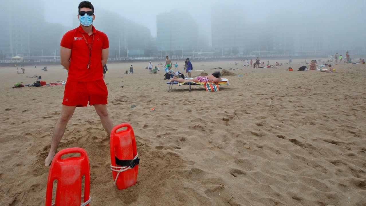 Personal de los equipos de socorrismo de Gijón, vigilan el baño de los usuarios de la playa de San Lorenzo