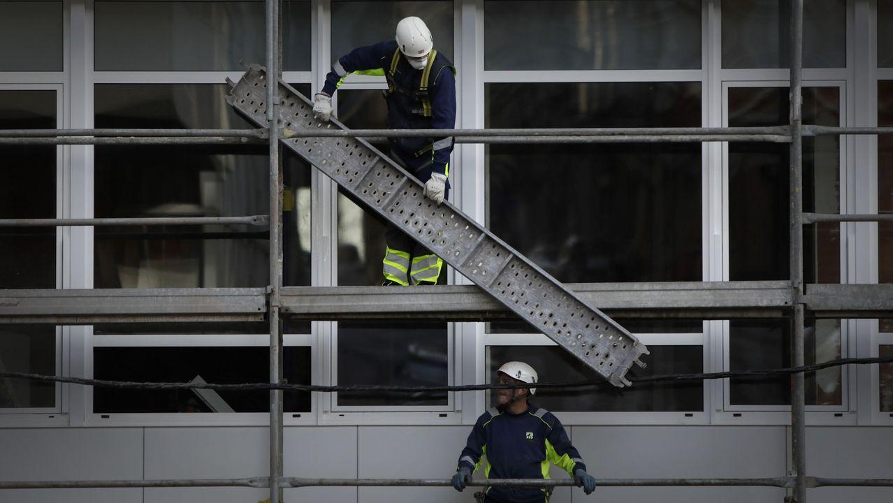 Operarios de Uncisa trabajan en un edificio de la avenida Fisterra
