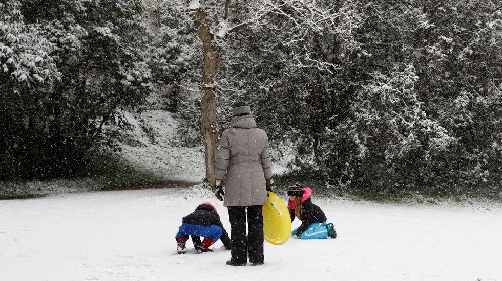 Una mujer mira cómo juegan sus hijos en la nieve