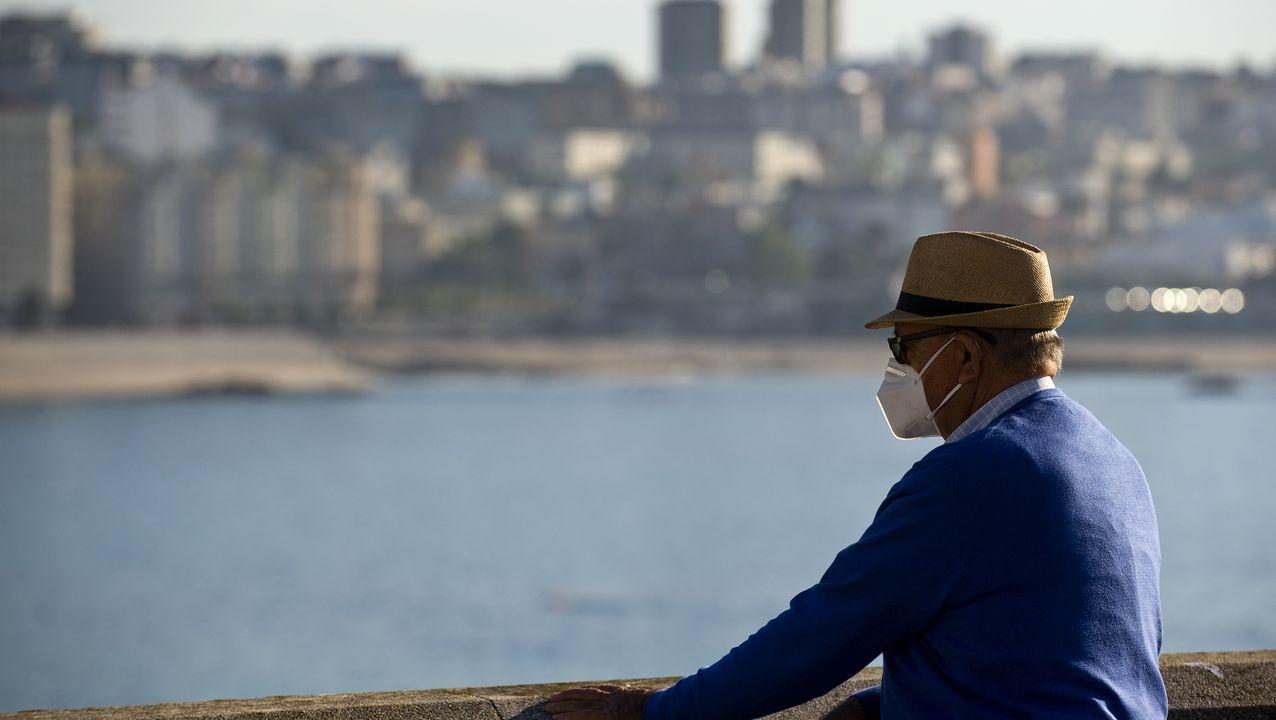 Un gijonés con la mascarilla bajada se sienta en el paseo del Muro, en Gijón, con la playa llena de paseantes