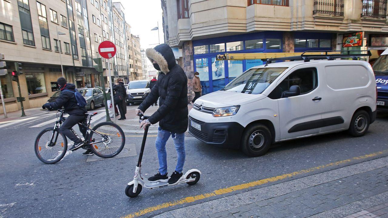 Una bicicleta y un patinete eléctrico circulan correctamente por la calzada en una calle del centro de Pontevedra