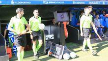 El trío arbitral del Deportivo-Real Oviedo pasa al lado de la pantalla del VAR