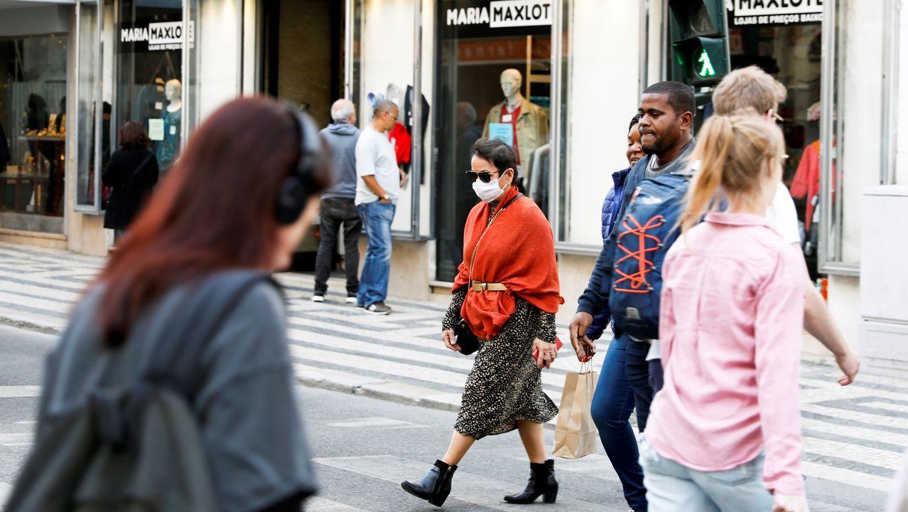 Imagen de transeúntes con mascarilla por Lisboa