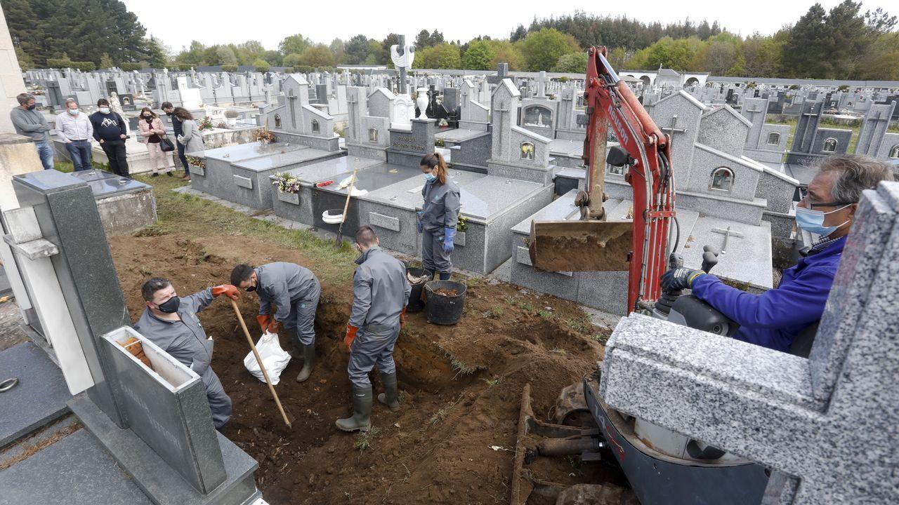 Los operarios realizan los trabajos de exhumación con la ayuda de una pequeña retroexcavadora