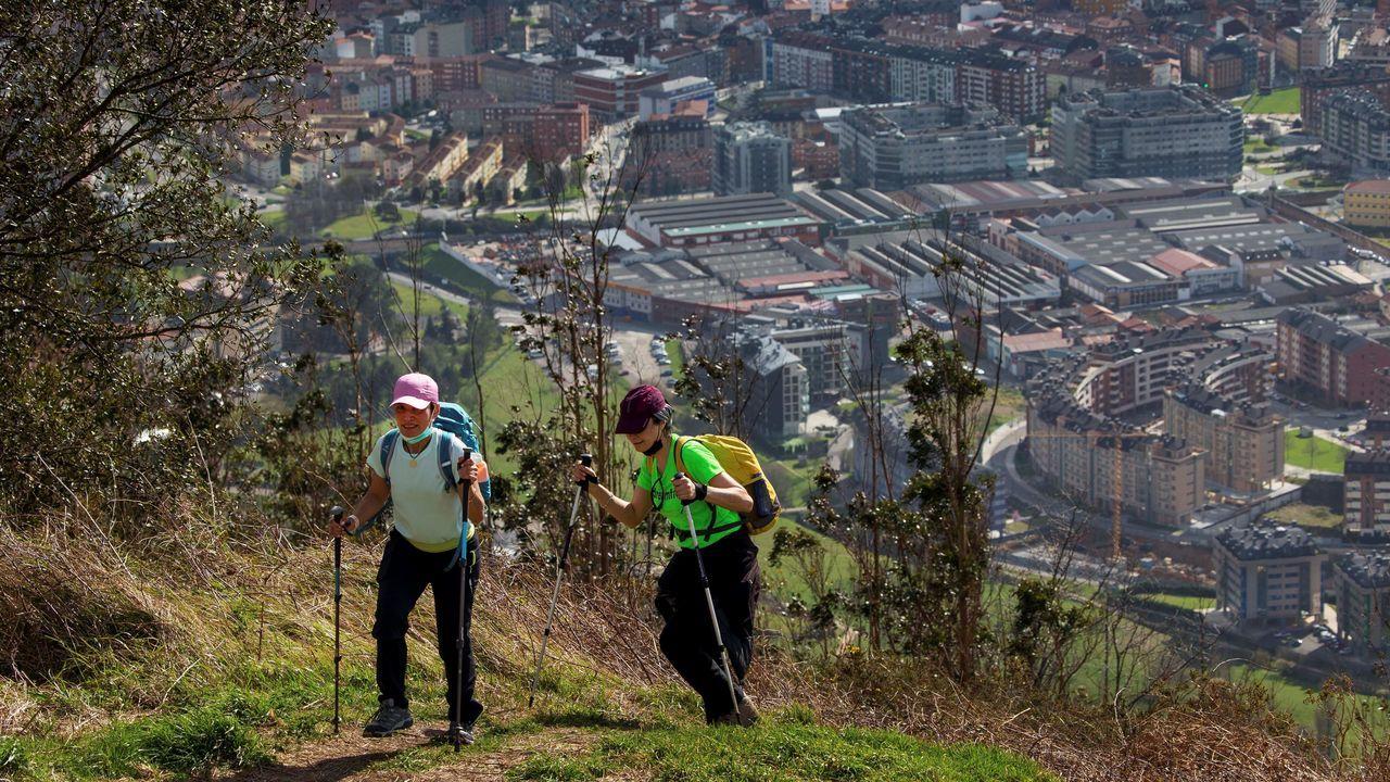 mole.Dos senderistas subiendo al monte Naranco con Oviedo al fondo