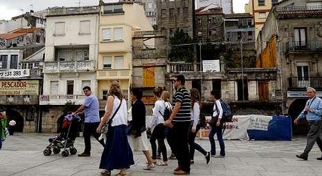 Los autobuses de excursionistas paran en O Berbés y los turistas transitan cada día por delante de la fachada en ruinas.