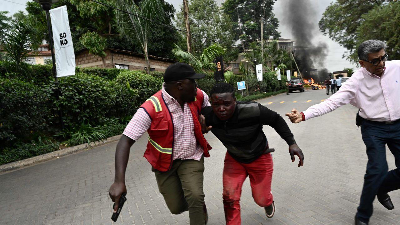 Miembros de las fuerzas de seguridad trasladan a un herido mientras la humareda causada por la explosión se eleva al fondo de la imagen