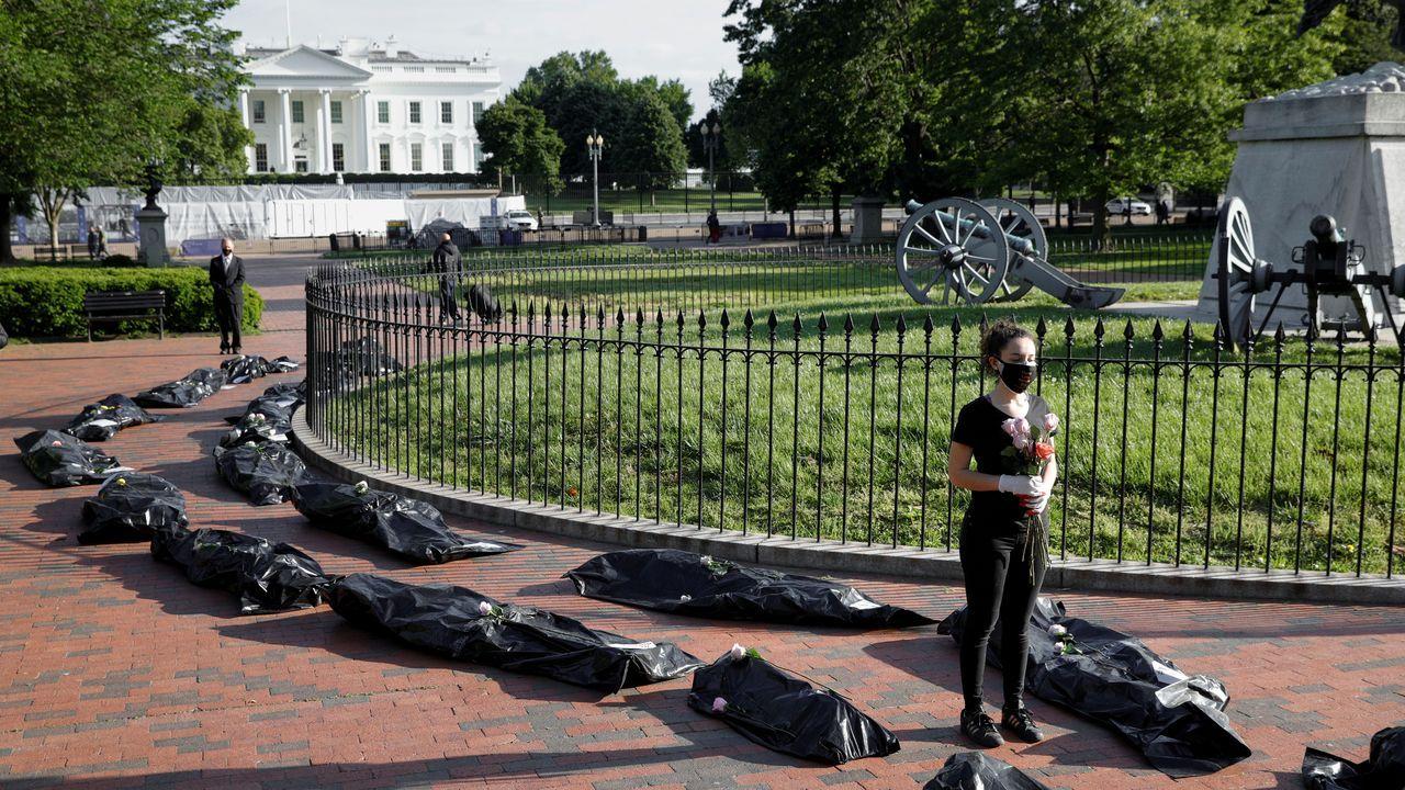 Unas cincuenta bolsas negras que simbolizaban los fallecidos por covid-19 fueron desplegadas frente a la residencia presidencial
