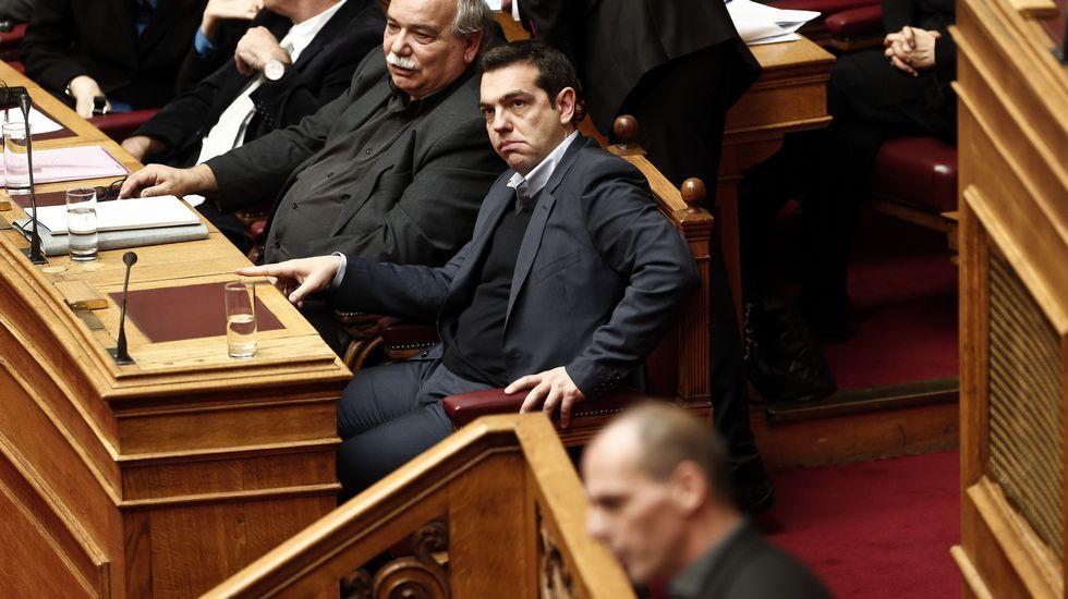 Tsipras escucha en el Parlamento la intervención de su ministro Yanis Varufakis.