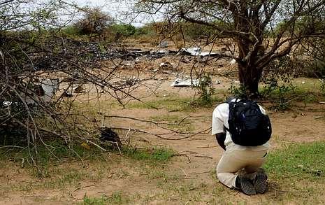El primer español enfermo de ébola.Un hombre reza arrodillado ante los restos del avión siniestrado cuando se dirigía a Argel.