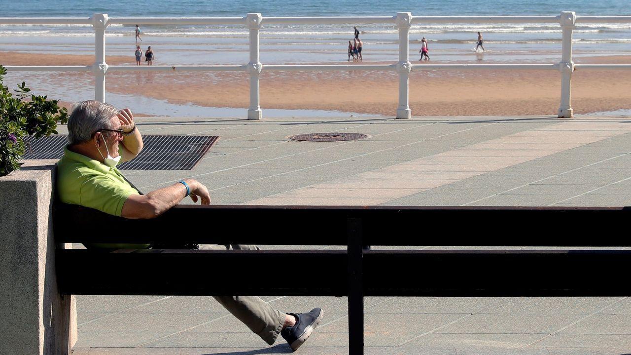 La EBAU, en pabellones y centros culturales.Un gijonés con la mascarilla bajada se sienta en el paseo del Muro, en Gijón, con la playa llena de paseantes