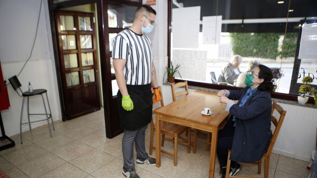 Un camarero atendiendo a una clienta en el bar A Morriña