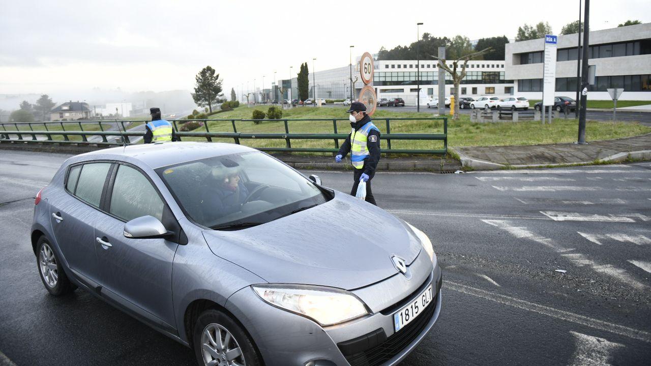 Reparto entrega de mascarillas por la Guardia Civil y Policía Local a trabajadores en la entrada del polígono industrial Lalin 2000