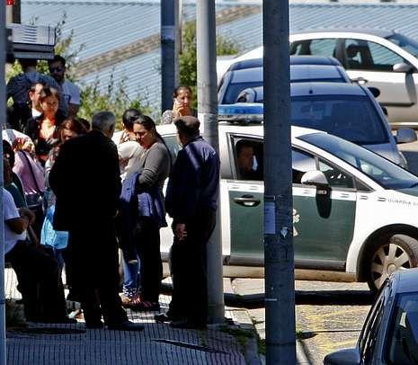 Los amigos de la banda ven cómo sale uno de los detenidos en un coche de la Guardia Civil.